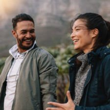 Portrait of happy young couple walking and talking in the countryside. Young man and woman enjoying on a nature hike.