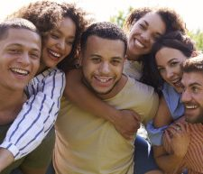Portrait of six young adult friends piggybacking outdoors